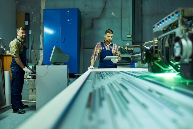 Workers operating laser engraving unit at factory