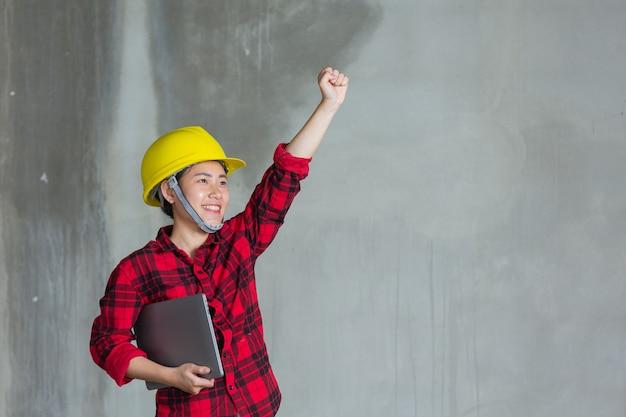 建設現場でラボトップを保持している労働者またはエンジニア