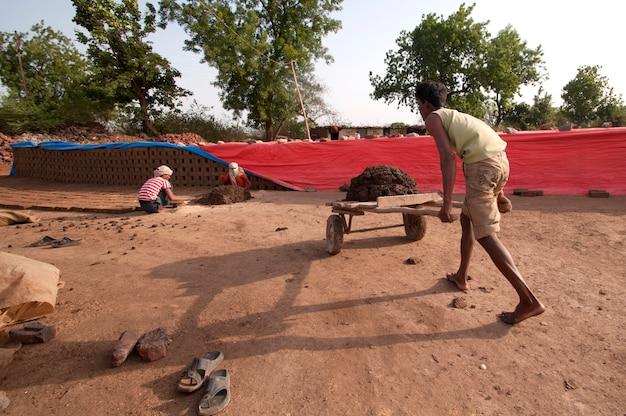 レンガ工場で伝統的なレンガを作るために粘土で処理する労働者