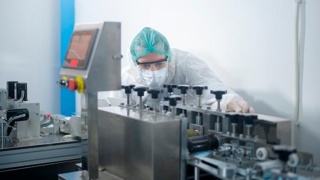 Рабочие, производящие хирургические маски на современном заводе, защита от covid-19 и медицинская концепция. Premium Фотографии