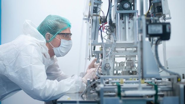 Workers producing surgical mask in modern factory, covid-19 protection and medical concept.