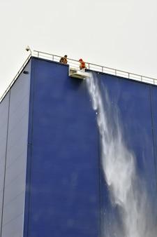 노동자들이 지붕에서 눈을 치우다