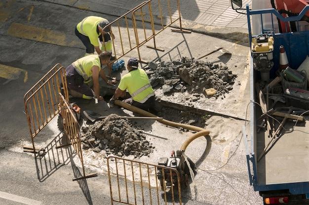 Workers repairing a broken water pipe on the road