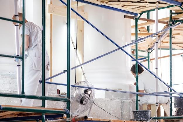 Рабочие восстанавливают белые стены на строительных лесах в большом помещении