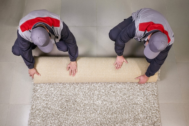 Workers rolling carpet on floor at home, view from above