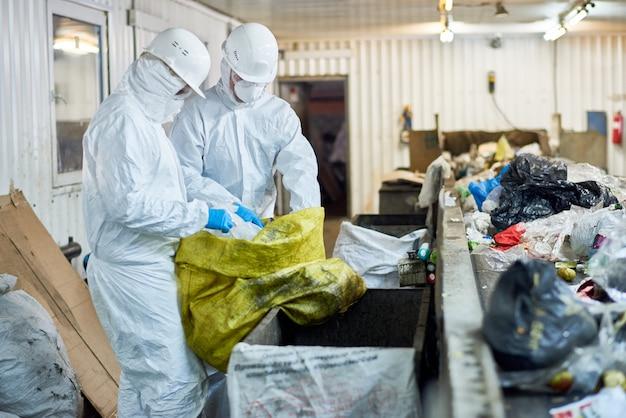 Рабочие, сортирующие перерабатываемые материалы на заводе по переработке отходов