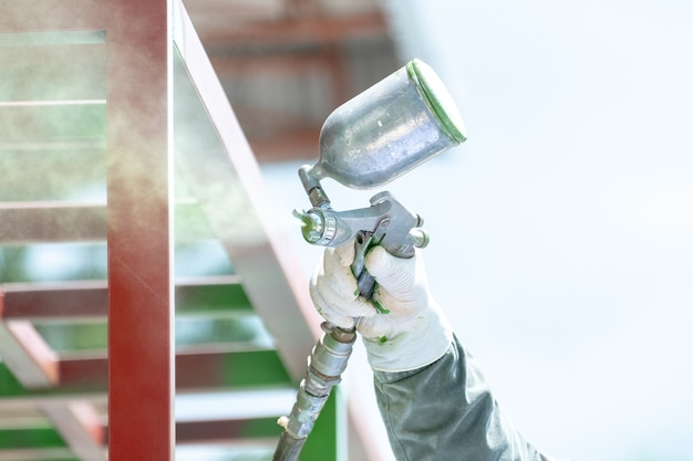 Рабочие, распыляющие краску на металлическую работу