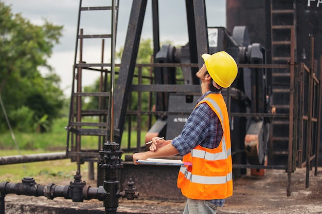 作業用オイルポンプの横に立って確認する労働者。