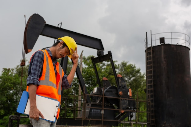 Рабочие стоят и проверяют у работающих нефтяных насосов.