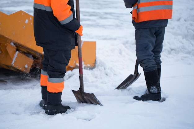 Workers sweep snow from road in winter