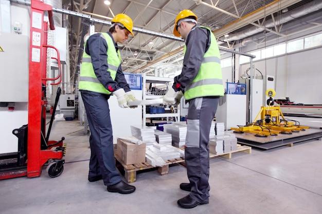 Рабочие принимают алюминиевые заготовки в цехе станков с чпу