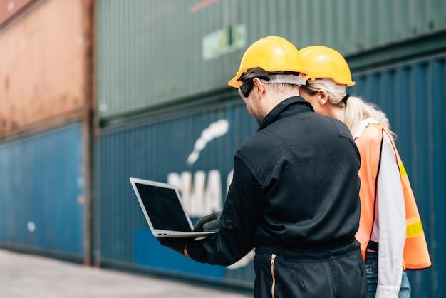 노란색 헬멧을 쓴 안전 점프수트를 입은 작업자들은 노트북을 사용하고 화물 컨테이너에서 이야기를 나누고 있습니다. 여성과 남성은 부두 창고에서 일합니다. 운송 수입, 수출 물류 산업