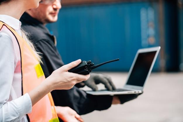 노동자 팀웍 남자와 노란색 안전모와 안전 죄수 복 작업복에 여자와화물 운송 창고에서 노트북 확인 컨테이너를 사용합니다.