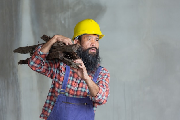建設現場で疲れて木を持っている労働者。労働者の日の概念