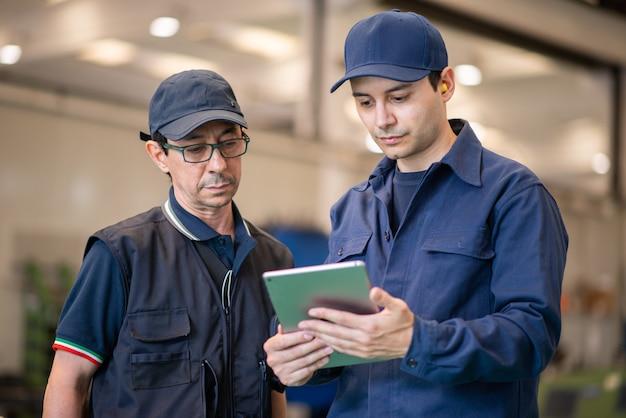 현대 공장에서 태블릿을 사용하는 근로자