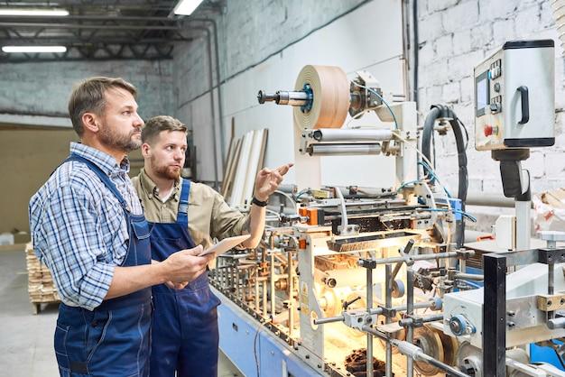 Рабочие, использующие современные машины на заводе