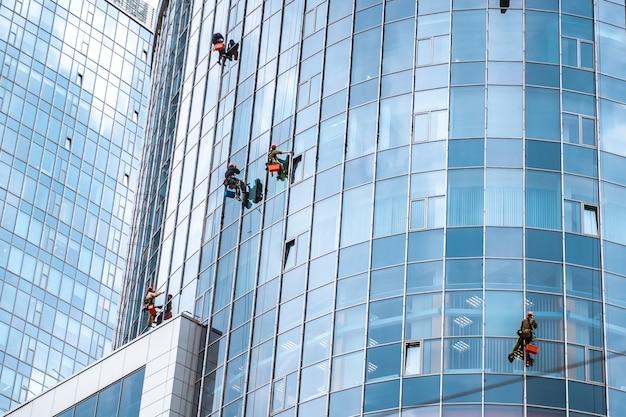 Рабочие моют окна в офисном здании