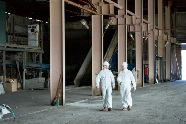 Workers wearing hazmat suits at factory