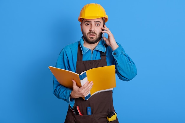 Workers wearing safety helmet, apron and uniform talking on mobile phone, having shocked facial expression, has problems on building, needs solving troubles, holding paper folder in hands.
