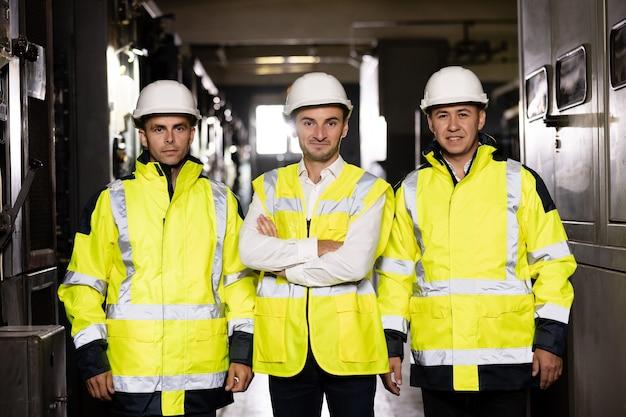 専門家のグループの焦点の合っていない背景の肖像画に安全制服とヘルメットをかぶっている労働者