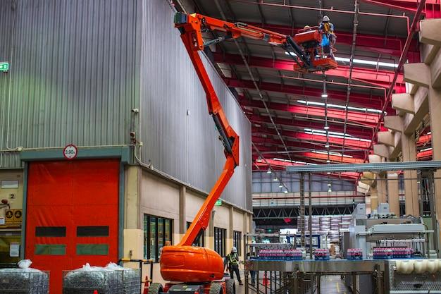 꼭대기 지붕으로 가는 붐 리프트를 위한 새로운 공장 산업의 건설 현장에서 일하는 노동자들