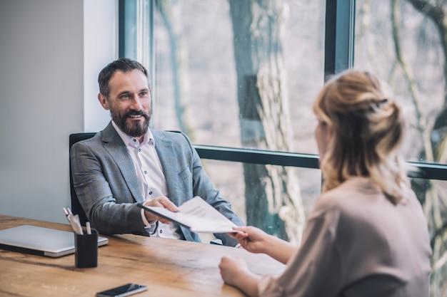ワークフロー。オフィスのテーブルに座っている女性アシスタントからドキュメントを取る灰色のスーツのビジネス大人の笑顔の男