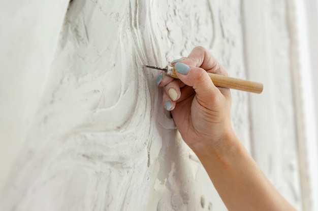 彫刻刀ツールを持つワークフロー女性が壁に浅浮き彫りの模様を彫る
