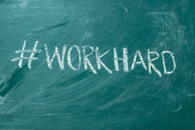 Workhard hashtag it handwritten with white chalk on a green blackboard.