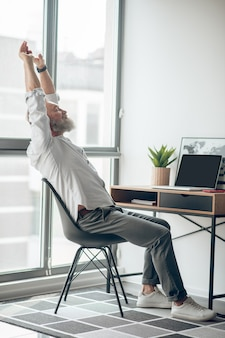 働く 。家で働いている成熟した自営業の男性は疲れているように見えます