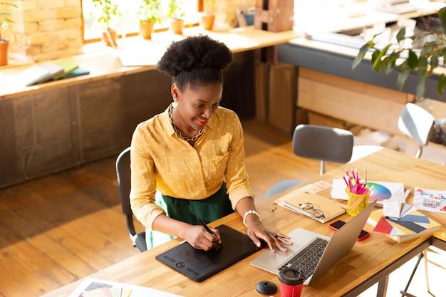一日中働いています。黄色いブラウスを着たクリエイティブマネージャーが、最新のテクノロジーを使って一日中働いています