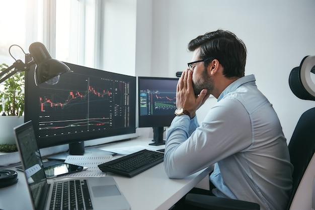 컴퓨터 차트 작업을 하는 피곤한 젊은 사업가나 상인의 하루 종일 보기