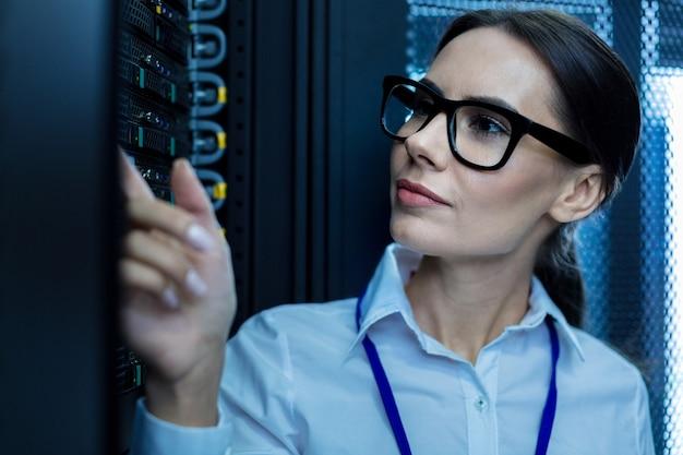 Работаю в одиночку. решительная задумчивая женщина думает и смотрит на оборудование