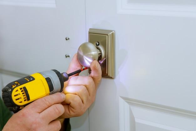 Working as handyman install new door lock in the room