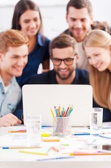 Работаем в команде. группа веселых деловых людей в элегантной повседневной одежде, вместе смотрящих на ноутбук и улыбаясь