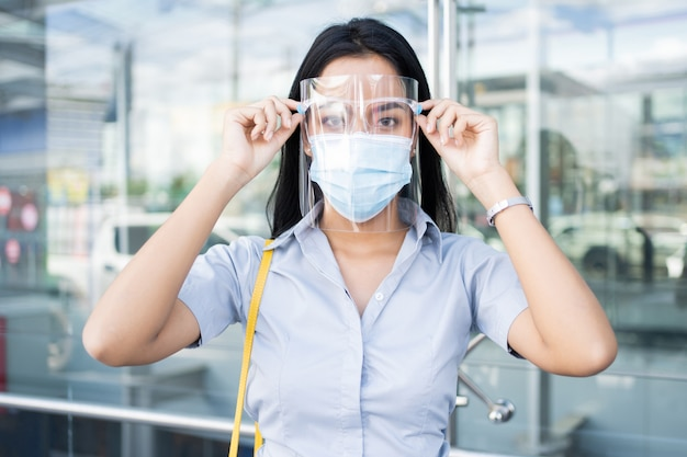 Working asian woman, he wears a mas and face shield to protect against viruses.
