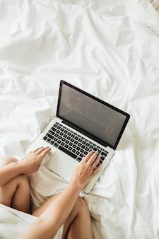집에서 일하는 개념. 소녀는 흰색 리넨과 침대에서 그녀의 노트북에서 일하고있다