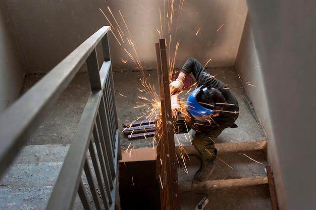 Работающие на стройке рабочие угловые шлифовальные машины