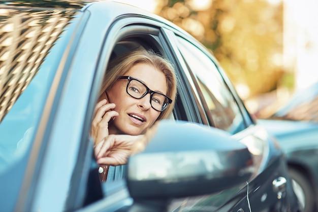 운전하는 동안 휴대 전화로 말하는 안경을 쓰고 바퀴 성숙한 비즈니스 여성에서 작업