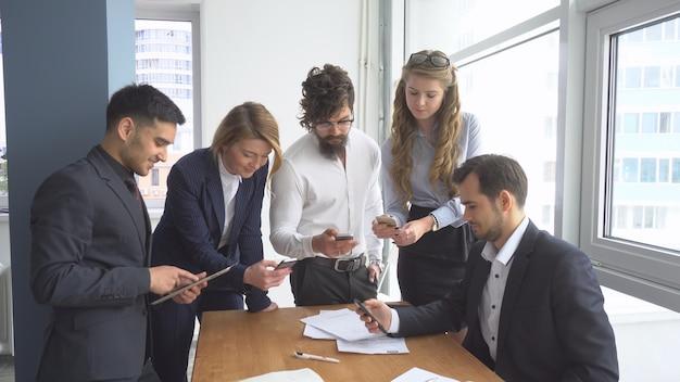 Рабочая атмосфера в офисе. группа деловых людей обсуждают вопросы бизнеса.