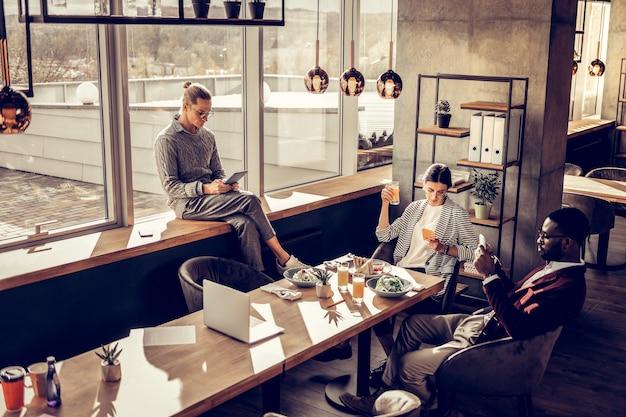 Рабочая атмосфера. довольно брюнетка девушка склоняет голову, глядя на экран телефона