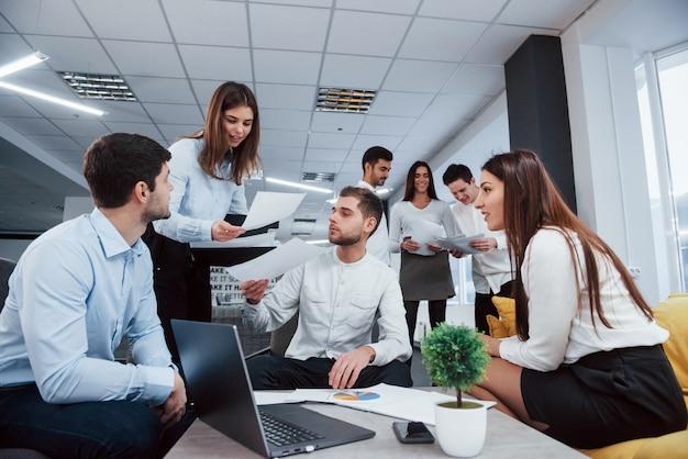 Рабочая, но веселая атмосфера. группа молодых фрилансеров в офисе разговаривают и улыбаются