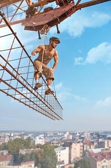 Lavorare con attenzione. un forte costruttore retrò senza camicia che guarda attentamente qualcosa in piedi su una traversa appesa a una gru a bassa angolazione