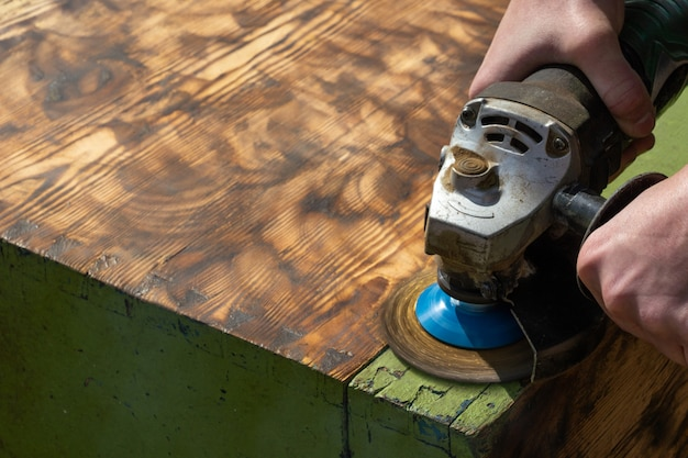 Working carpenter grinds wood, removing old paint
