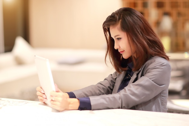Working and charming woman with glasses using tablet portrait herself