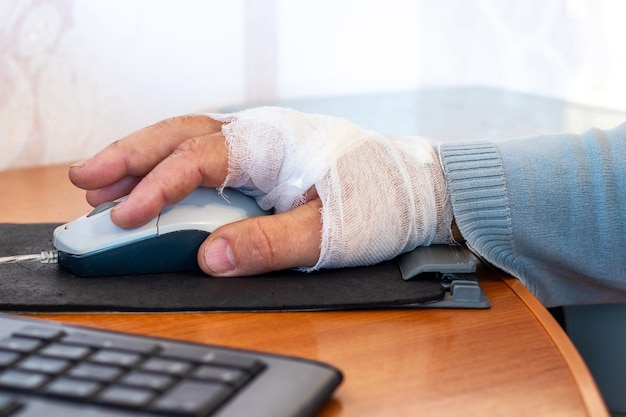 Working at a computer with an injured arm, a man with a bandaged arm with a computer mouse