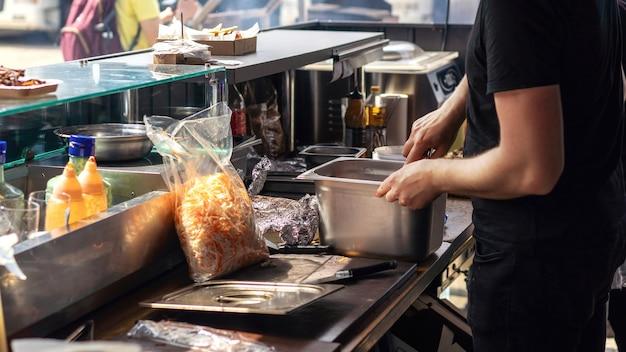 바베큐 트럭에서 일하는 요리사가 주문을 하고 있습니다. 길거리 음식