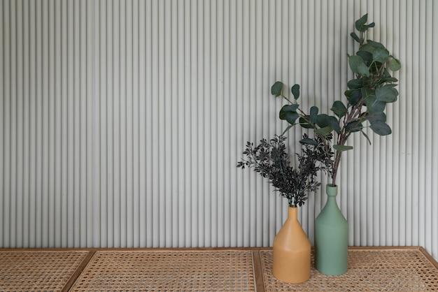 マスタードカラーと緑のセラミック花瓶で装飾された作業コーナー、自然な光の設定シーン/アパートのインテリア/コピースペースの自然な籐製ベンチの中に人工植物が入っています