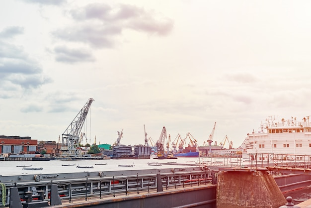 Работают крановые мосты на верфи и грузовые корабли в порту