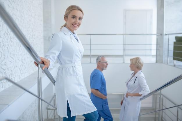 就業日。病院の階段に立って話している専門医のグループ