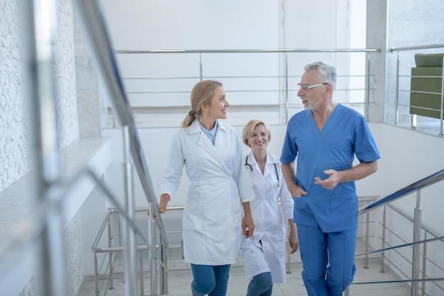 Рабочий день. группа профессиональных медицинских работников поднимается наверх, что-то обсуждает